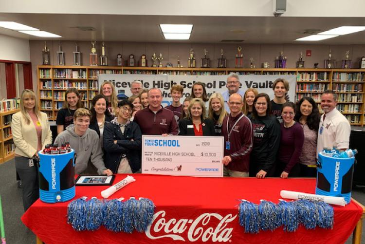 "Niceville High School Track and Field team members accept $10,000 check from the Coca Cola Company for winning the POWERADE ""Power Your School"" competition."